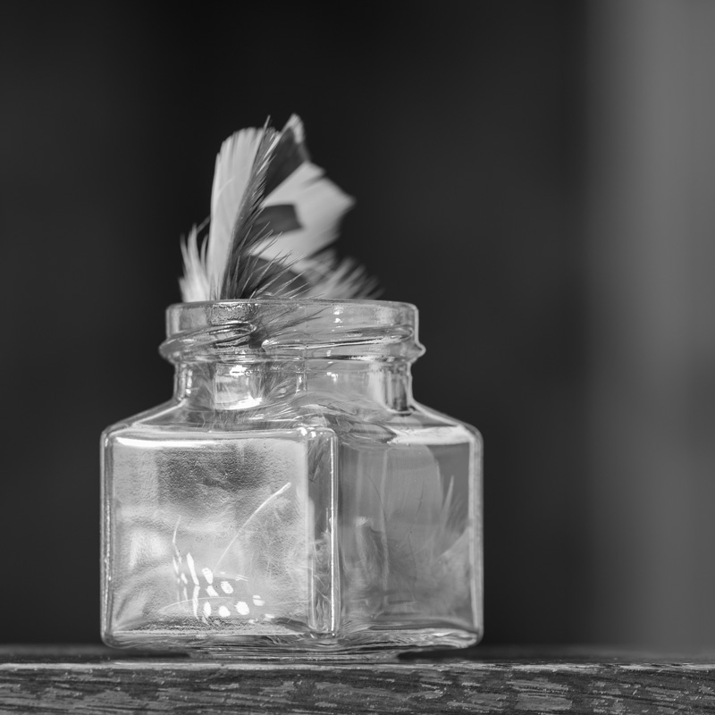 Glass bottle with feathers